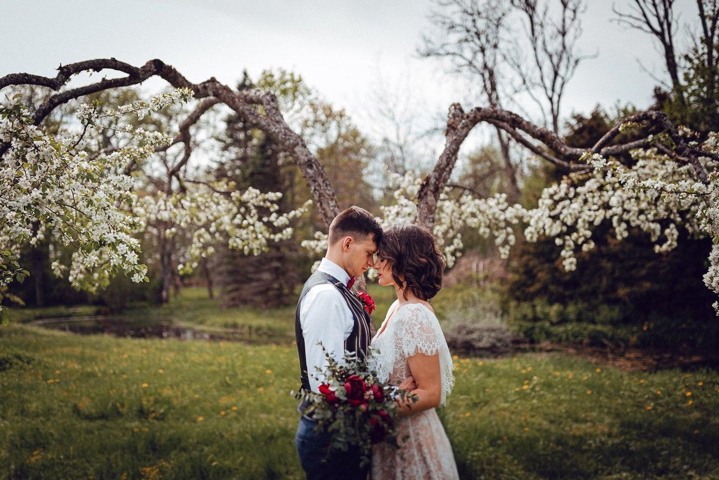 Jaunā pāra kāzu fotosesija ziedošā ābeļdārzā.