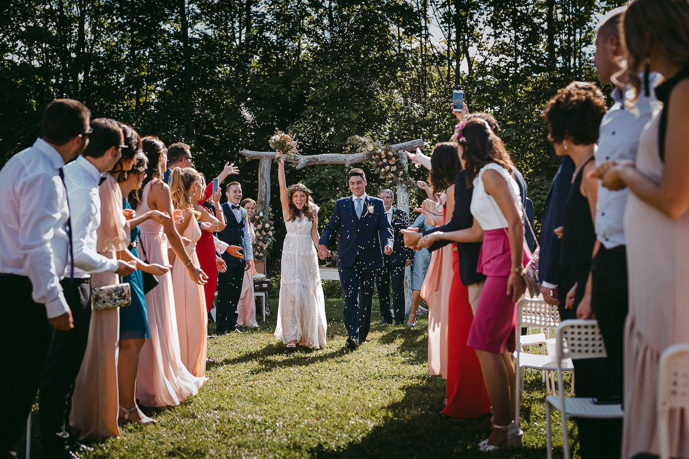 Jaunā pāra emocija pēc kāzu ceremonijas brīvā dabā. Tradīcija ar rīsu mešanu.