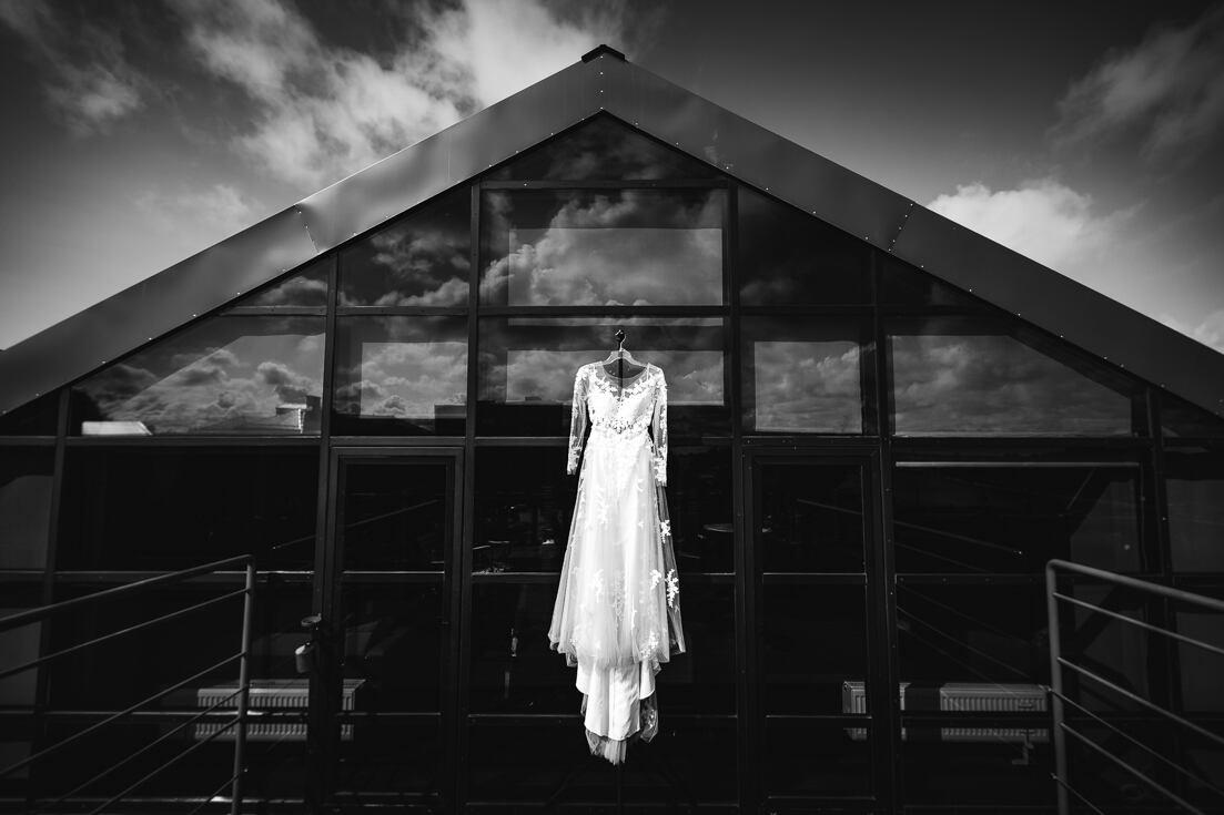 Līgavas kleita, kas atradusi vietu Liepājas viesnīcas Hotel Promenāde numuriņa terasē. Kāzu fotogrāfs Juris Zīģelis.