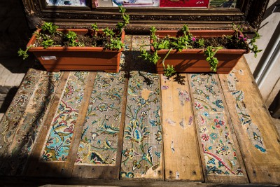 Nevajadzīgie paklāju dizaina šabloni labi izdaiļo galda virsmu. Kashan, bazaar.