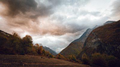 Ielejas krāsu saspēle ar rieta mākoņiem. Albānija, Valbones ielejas nacionālā parka kalnos.